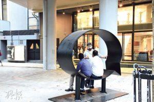 陳明柱多次強調,不少藝術家均希望參觀者可與作品互動,如放置於香港藝術中心門外、由美國藝術家Hank Willis Thomas製作的《Ernest and Ruth》,為金屬製成的對話框,數名途人坐在其中對話,便深化了作品的意義。(圖:鄭律銘)