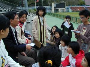 香港足球總會總幹事林俊英(左二)坐在球場中的觀眾席椅子上,一一解答校園記者的提問。