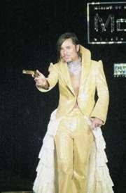 甘國亮曾5次獲選「十大最傑出衣著人士」,其衣著品味受大認同。圖為甘國亮出席2001年十大最傑出衣著人士頒獎典禮的打扮,一身金色西裝配一支金手槍,有型有款。(資料圖片)