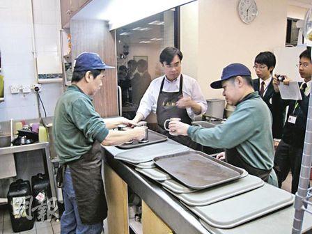 東華三院自在軒員工黃基騰(左)畄好飲品後,交給另一員工陳有帶(右)放到桌面,餐飲服務經理(中)從旁指導。(梁以祈攝)