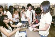 校記當中不少是李敏的「忠實讀者」,訪問結束後,紛紛變成小粉絲,拿出著作向李敏索取簽名。(圖﹕董玉金)