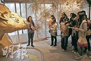 大會工作人員(左)向校記講解「伙炭藝術工作室開放計劃2010」特備展覽《如果你停泊在這裏》,並邀請校記思考他們認為重要的問題。(傳媒teen使 黎影喬、呂智良攝)