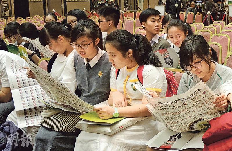 校記到場後,在開學禮開始前翻閱報紙,在校記版面的眾多相片中找尋自己或同學的臉孔。