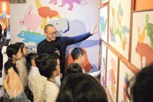 本地藝術家林東鵬(持咪者)向「藝術小導賞」的學員簡介玩具亭內的擺設。