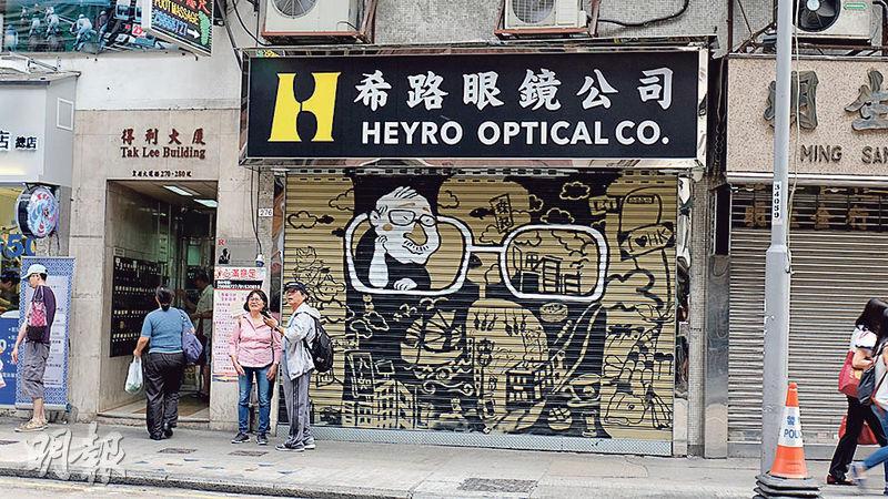 希路眼鏡公司的鐵閘畫作上,老闆周先生從眼鏡框中鑽出來,俯視西營盤這些年來的變遷,展現出店主緬懷的西營盤。