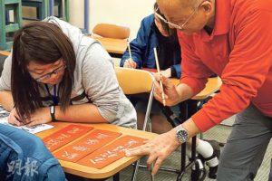 黃誠業(右)教導校記寫好書法的正確方法
